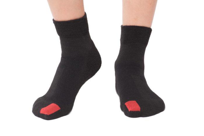plus12socks Socken schwarz an Kinderfüssen Vorderansicht
